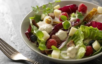 Salat med kylling, dijonnaise, salte mandler, rugbrødscrouton, danbo, bær og urter