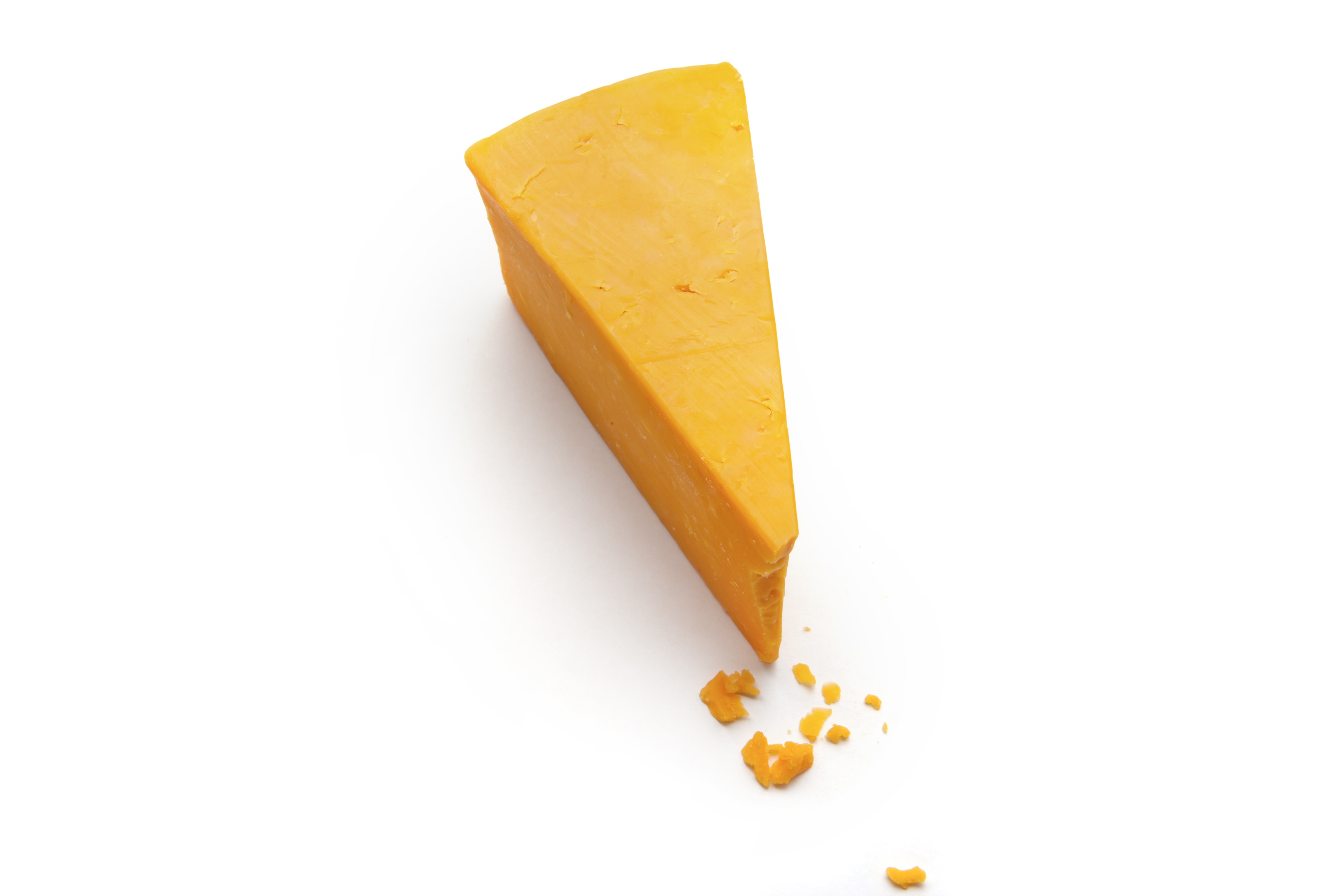 a wedge and some crumbs of cheddar cheese on a white studio background.